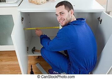 Reparador sonriente midiendo algo