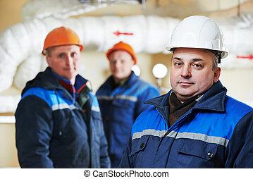 Reparadores de ingenieros de calefacción en la sala de calderas