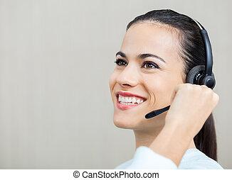 Representante de servicio al cliente hablando por los auriculares