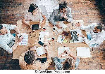Resultados y trabajo en equipo. La mejor vista del grupo de seis personas discutiendo algo mientras están sentados en la mesa de la oficina