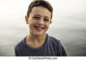 Retrato al aire libre de adorable niño junto al lago al atardecer