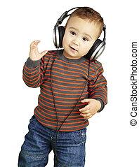 Retrato de adorable niño con auriculares escuchando música agai