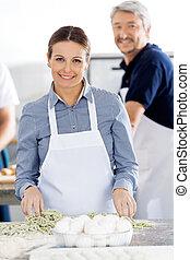 Retrato de chefs felices preparando pasta en la cocina