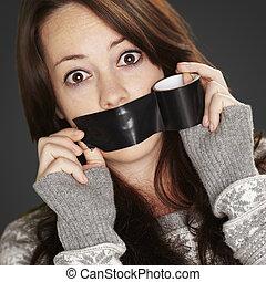 Retrato de chica asustada siendo silenciada por sí misma sobre un bac negro