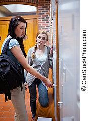 Retrato de estudiante abriendo su casillero mientras hablaba con su amiga en un pasillo
