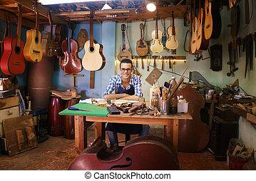 Retrato de feliz artesano lute creador en la tienda de guitarras sonriendo a la cámara