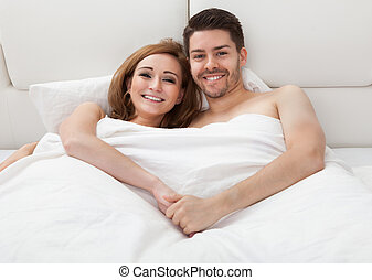 Retrato de feliz pareja en la cama