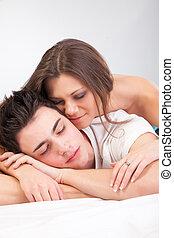 Retrato de feliz pareja joven acostado en la cama y sonriendo
