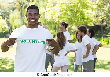 Retrato de feliz voluntaria sosteniendo camiseta