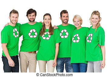 Retrato de grupo de gente que lleva camisetas de símbolos de reciclaje