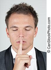 Retrato de hombre de negocios mostrando un gesto de silencio con su dedo índice por la boca