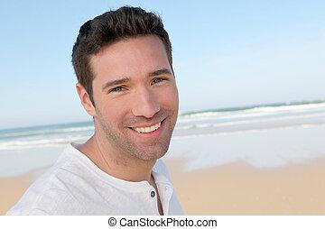 Retrato de hombre guapo en la playa