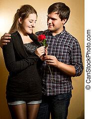 Retrato de hombre sonriente dando rosa roja a novia linda
