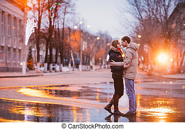 Retrato de joven hermosa pareja besándose en un día lluvioso de otoño.