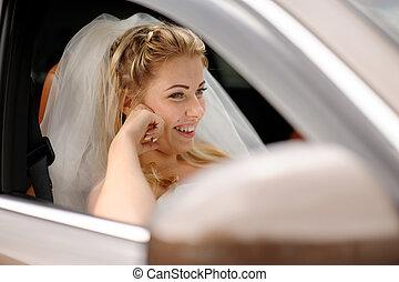 Retrato de la novia feliz en un coche