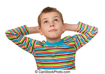 Retrato de niño en blanco, sonriendo, mira con las manos detrás de la cabeza.