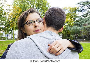 Retrato de pareja de amor abrazando al aire libre en el parque luciendo feliz