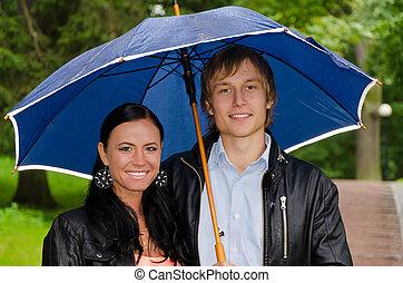 Retrato de parejas jóvenes bajo el paraguas del parque