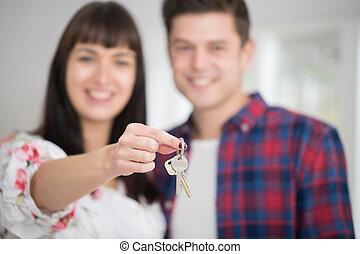 Retrato de parejas jóvenes con llaves de un nuevo hogar