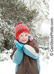 Retrato de un chico feliz al aire libre en la nieve.