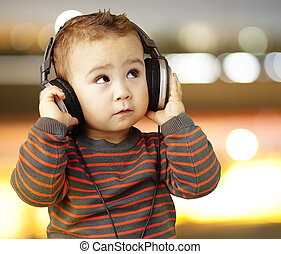 Retrato de un chico guapo escuchando música mirando a la ciudad