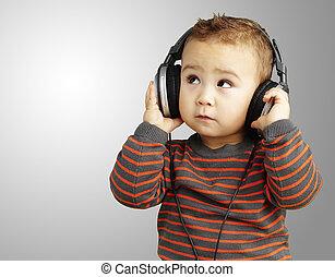 Retrato de un chico guapo escuchando música mirando hacia arriba