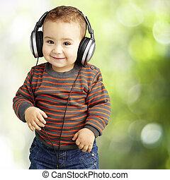 Retrato de un chico guapo escuchando música y sonriendo a par