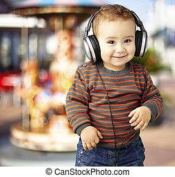 Retrato de un chico guapo escuchando música y sonriendo de nuevo