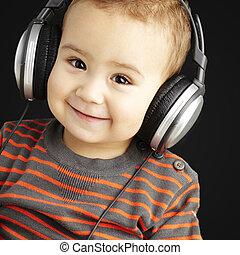 Retrato de un chico guapo escuchando música y sonriendo por B