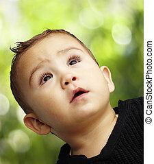 Retrato de un chico guapo mirando hacia un backgroun natural