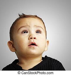 Retrato de un chico guapo mirando hacia un fondo gris,