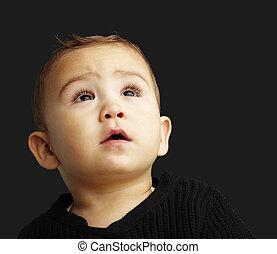 Retrato de un chico guapo mirando hacia un fondo negro