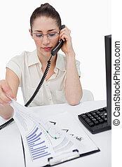 Retrato de un director serio haciendo una llamada telefónica mientras mira las estadísticas en un fondo blanco