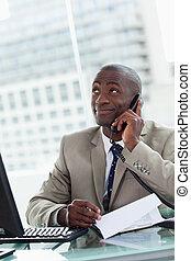 Retrato de un empresario feliz haciendo una llamada mientras leía un documento en su oficina