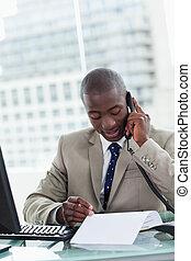 Retrato de un empresario haciendo una llamada mientras leía un documento en su oficina