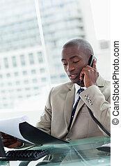 Retrato de un empresario serio haciendo una llamada mientras leía un documento en su oficina