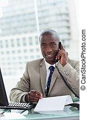 Retrato de un empresario sonriente haciendo una llamada mientras leía un documento en su oficina