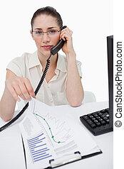 Retrato de un gerente haciendo una llamada telefónica mientras mira las estadísticas contra un fondo blanco