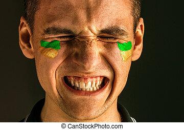 Retrato de un hombre con la bandera del Brasil pintado en su cara.