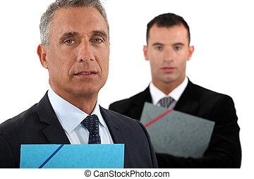 Retrato de un hombre de negocios con su asistente detrás de él