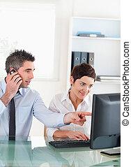 Retrato de un hombre mostrando algo a su compañero de trabajo en una computadora en una oficina