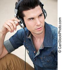 Retrato de un joven guapo escuchando música con auriculares
