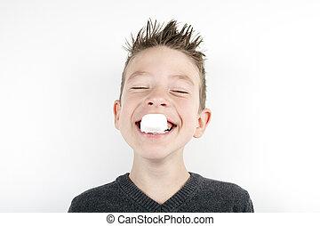 Retrato de un lindo niño alegre con un malvavisco