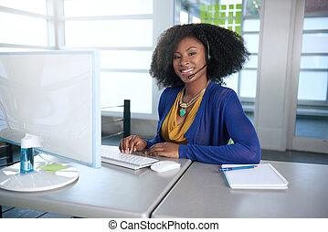 Retrato de un sonriente representante de servicio al cliente con un afro en la computadora usando auriculares