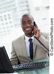 Retrato de un trabajador sonriente haciendo una llamada telefónica