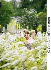 Retrato de una chica en un arbusto blanco