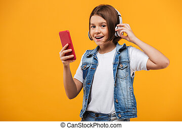 Retrato de una colegiala feliz escuchando música