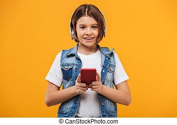 Retrato de una colegiala sonriente escuchando música