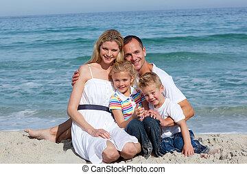 Retrato de una familia alegre sentada en la arena