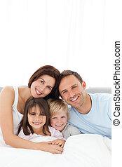 Retrato de una familia alegre sentada en la cama
